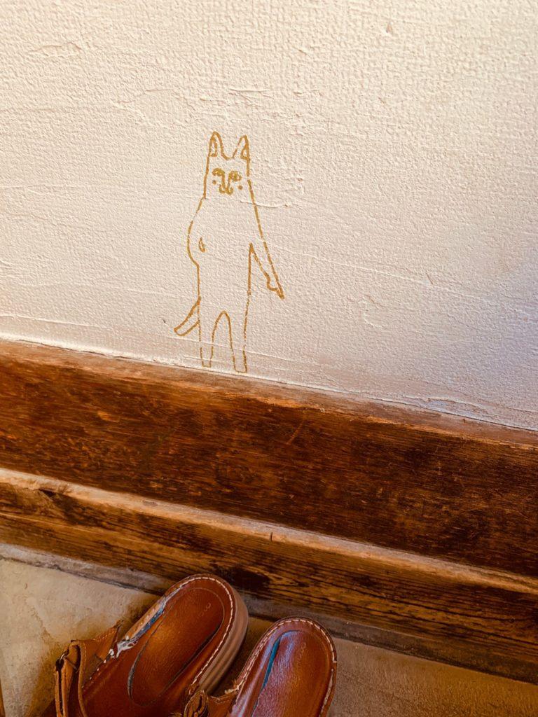 猫ちゃんが靴を脱ぐ場所を指差し